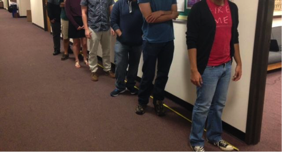 Image of people waiting in a line in a hallway, no faces shown.
